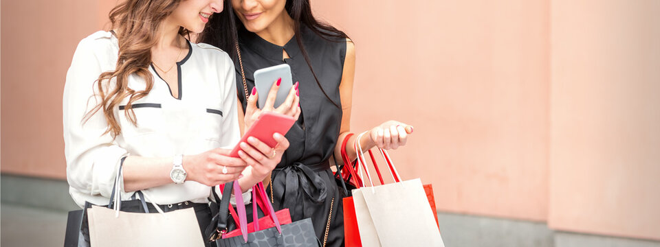 Two beautiful caucasian young women watching at smart phone on new seasonal offers with bags during shopping near wall of shopping mall