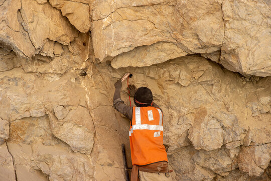 A Border Roads Organisation (BRO) worker puts dynamite sticks to blast rocks on an under construction highway in the Ladakh region