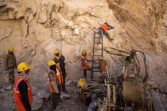 Border Roads Organisation (BRO) workers put dynamite sticks to blast rocks on an under construction highway in the Ladakh region