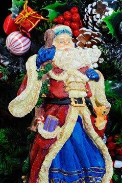 Ceramic Father Christmas against a Christmas wreath.