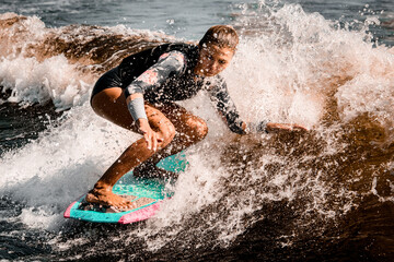 Active woman stands with bent knees on surf style wakeboard and ride on wave