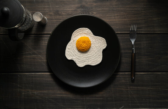 Knitted fried eggs on a plate. Synthetic food. Top View. Dark wooden surface.