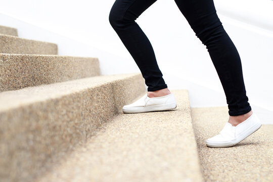 stairway. Close up legs and shoes sneakers of young woman one person walking stepping going up the stairs in modern city, success, grow up.