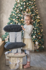 pretty little girl in white knitted sweater near christmas tree