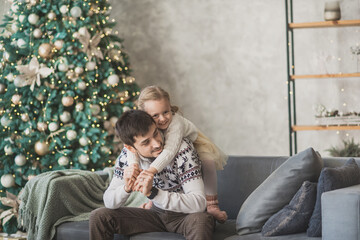 a dad anad a daughter sit on the sofa in christmas decorated living room