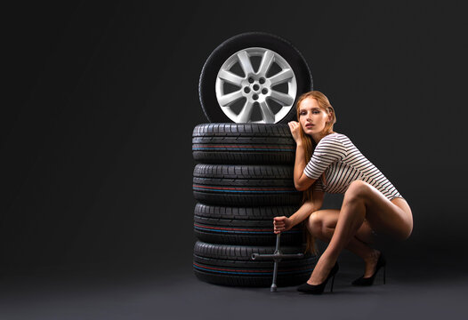 New tires stack and beautiful girl with wrench on a dark background. Copy space.