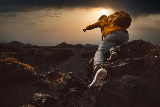 Successful hiker hiking a mountain pointing to the sunset. Wild man with backpack climbing a rock over the storm. Success, wanderlust and sport concept.