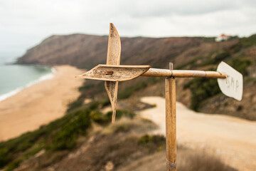 Wooden windmill above the cliff by the beach (Portugal).