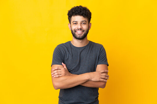 Young Moroccan man isolated on yellow background keeping the arms crossed in frontal position