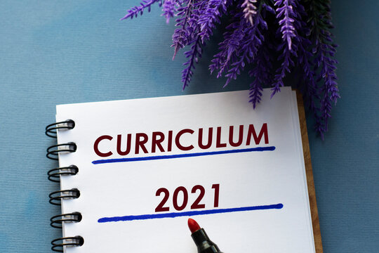 CURRICULUM 2021- written in a notebook on a gray background with branches of lavender