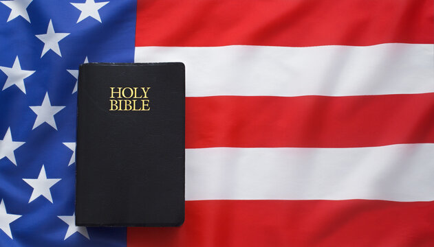 Holy Bible on American Flag. Flat lay view.