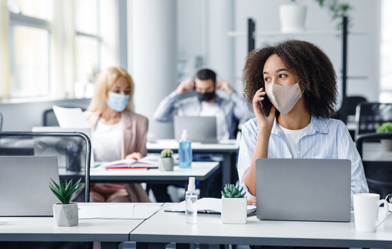 Working with clients after returning from quarantine. African american woman in protective mask speaks on phone, sitting with colleagues