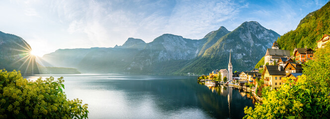 Papiers peints Navire Panorama view of famous old town Hallstatt and alpine deep blue lake with tourist ship in scenic golden morning light on a beautiful sunny day at sunrise in summer, Salzkammergut, Austria