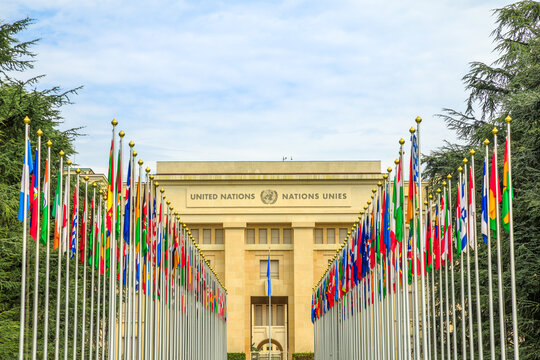 Geneva, Switzerland - Aug 16, 2020: Row of flags at entrance of United Nations Offices or Palais des Nations in Ariana Park, on shore of Lake Geneva. Since 1966 is main European headquarters of UN.