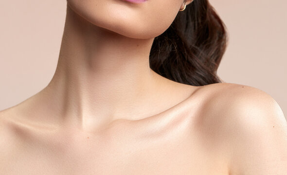 Women's neck and shoulders skincare brown hair on a nude background