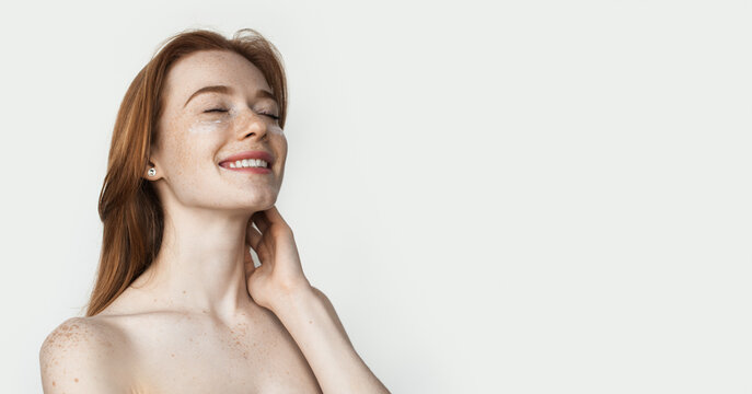 Ginger lady with freckles is wearing anti aging eye patches posing on white studio wall with naked shoulders advertising something