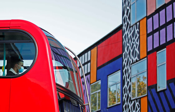A man wearing a face mask travels on a bus, as it drives past a mural created by artist Camille Walala in Leyton, London