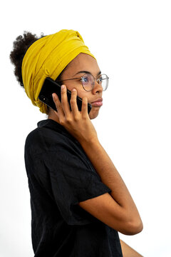 Portrait of young woman wearing glasses and yellow head scarf and speaking on mobile phone over white background