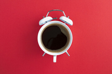 Top view of coffee on the dial of the white alarm clock in the center of the red background