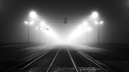 Paintings on glass Bridges Tramway track and asphalt road (highway) through the illuminated empty Stone bridge in a thick fog at night. Lanterns close-up. Daugava river, Riga, Latvia. Concept image, black and white, monochrome