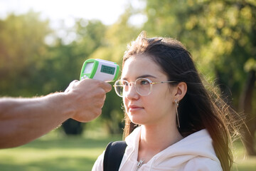 Measuring of temperature of teenage girl outdoor with infrared electronic thermometer. Health care and education concept