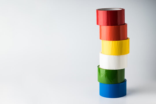 Colored adhesive tape rolls on light background