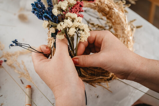 Girl making floral door wreath using colorful dry summer flowers and plants.  Fall flower decoration workshop
