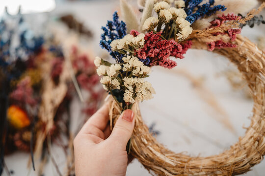 Girl making floral door wreath from colorful dry summer flowers and plants.  Fall flower decoration workshop