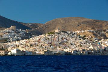 Budynki Greckiej wyspy Siros widziana od strony morza w pogodny dzień