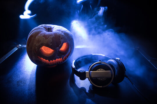 Halloween pumpkin on a dj table with headphones on dark background with copy space. Happy Halloween festival decorations