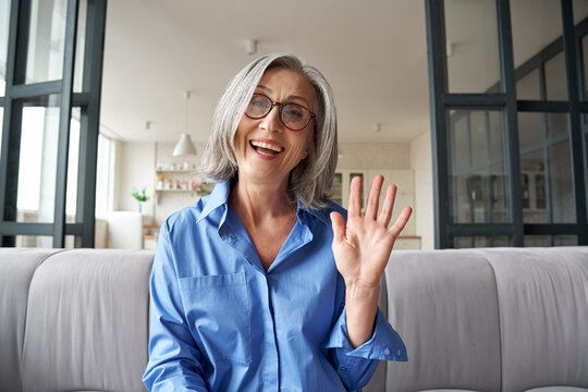 Happy mature middle aged woman online teacher waving hand talking to web cam video conference calling in virtual webcamera chat meeting by distance remote vidoecall. Headshot portrait. Webcam view.