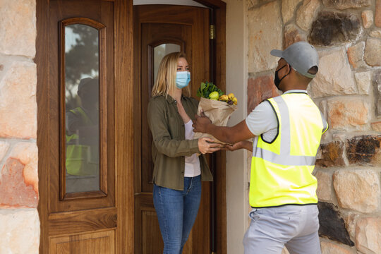 Delivery man delivering groceries to woman wearing face mask at home