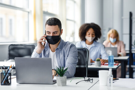 Customer consultation by phone remotely at returning to work after quarantine. Millennial man in protective mask with smartphone looks at laptop at workplace