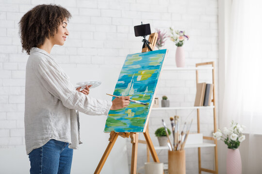 Art, hobby and recording streaming video for drawing blog. Young african american lady paints picture of landscape with paintbrush and watches lesson on smartphone