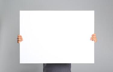 Obraz Man holding white blank poster on grey background. Mockup for design - fototapety do salonu