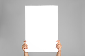 Fototapeta Man holding white blank poster on grey background, closeup. Mockup for design obraz