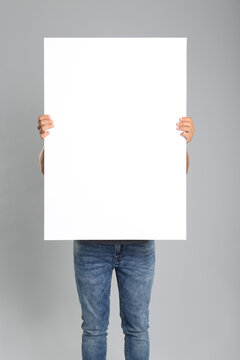 Man holding white blank poster on grey background. Mockup for design