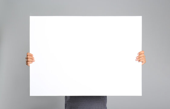 Man holding white blank poster on grey background. Mockup for design