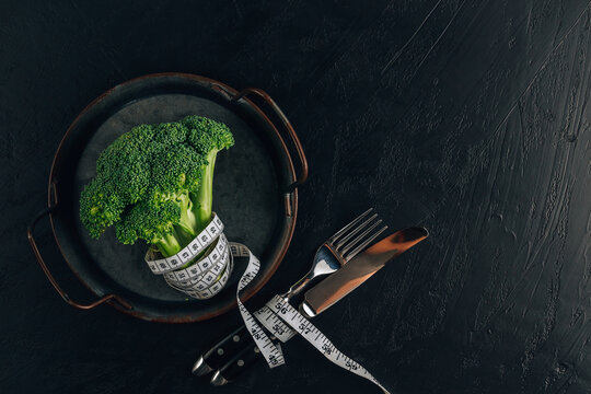 Concept of healthy dieting with broccoli on black stone background