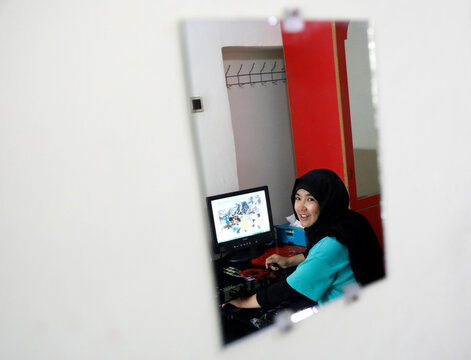 Fatima Sultani, 18 a member of Hikeventures mountaineering team, is reflected in a mirror as she uses a computer at her house in Kabul
