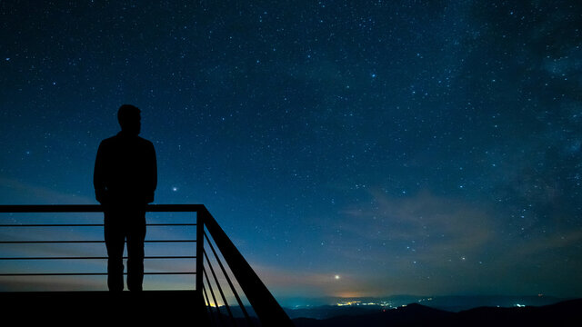 The man standing on the balcony on the starry sky background