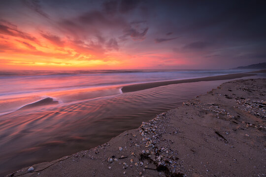 Amazing view with colorful reflections on the beach at sunrise