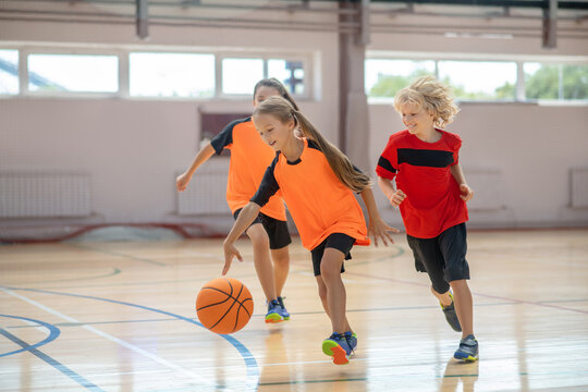 Children in bright sportswear playing basketball and looking excited