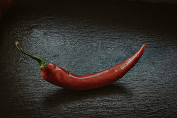 Red hot chili pepper on the black stone surface