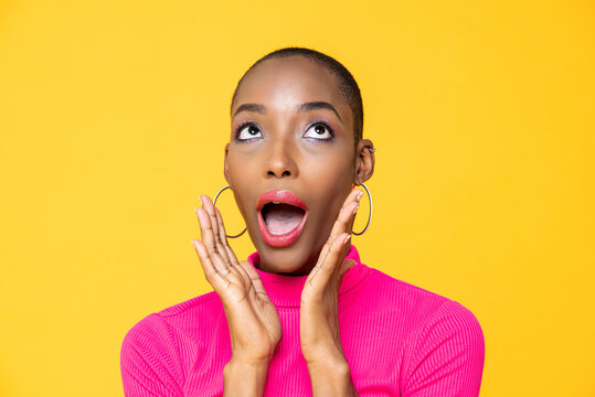 Close up portrait of surprised young African American woman looking upward with hands cupped around mouth isolated on studio yellow background