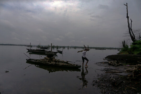 A man carries a piece of wood from a canoe in Ogoniland, Rivers State