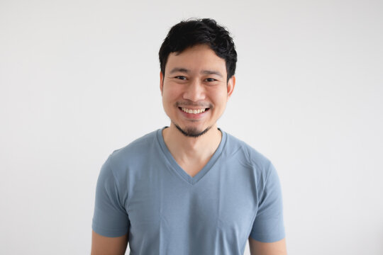 Portrait of happy Asian man in blue t-shirt on isolated white background.