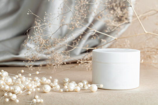 Closeup white jar of moisturizing niche luxury cream on background of beige fabric drapery. Cosmetics, products for care and personal hygiene concept. Minimalist packing, branding.