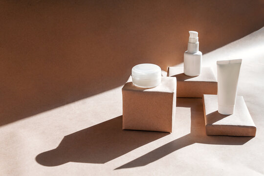 White tube, bottle, jar of cream, lotion, gel on podiums on craft background with shadows. Cosmetics, products for care and personal hygiene concept. Minimalist packing, branding.
