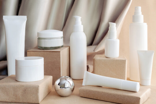 White tubes, bottles, jars of cream, lotion, gel on podiums on background of fabric drapery. Cosmetics products for care and personal hygiene concept. Minimalist packing, branding.